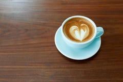 一个杯子与心脏形状拿铁艺术的热的拿铁咖啡在黑褐色木头桌上 免版税库存照片