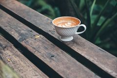 一个杯子与心脏拿铁艺术的热的拿铁咖啡在长木凳在绿色自然背景中 库存图片