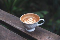 一个杯子与心脏拿铁艺术的热的拿铁咖啡在长木凳在绿色自然背景中 免版税库存照片