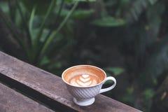 一个杯子与心脏拿铁艺术的热的拿铁咖啡在长木凳在绿色自然背景中 免版税库存图片