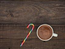 一个杯子与泡沫的可可粉和在一张木桌上的甜糖果 免版税图库摄影