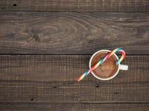 一个杯子与泡沫的可可粉和在一张木桌上的甜糖果 免版税库存照片