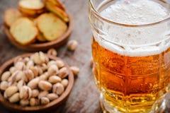 一个杯子与泡沫的在一张木桌上的低度黄啤酒和开心果 免版税库存照片