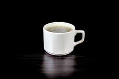 一个杯子与泡沫的拿铁在黑桌上 免版税库存照片