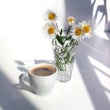 一个杯子与泡沫的无奶咖啡,白色春黄菊花花束在一个水晶花瓶的用在一张白色桌上的水在阳光下 库存照片