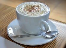 一个杯子与泡沫的热奶咖啡 免版税库存图片