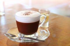 一个杯子与泡沫的热巧克力在上面和变甜的浓缩牛奶射击在木桌上的在咖啡馆 免版税库存图片