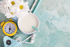 一个杯子与秸杆、耳机和时钟的牛奶 免版税库存照片