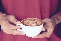 一个杯子与美好的拿铁艺术的热奶咖啡咖啡在人手上 免版税库存照片
