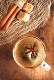 一个杯子与美洲黑杜鹃的加香料的咖啡担任主角和cinamon棍子和sug 免版税库存照片