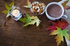 一个杯子与被编织的毯子、坚果、蜡烛和秋叶的热的可可粉在一张土气木桌上 免版税库存图片