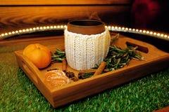 一个杯子与manadarines片断的温暖的茶在一个木盘子的 库存图片