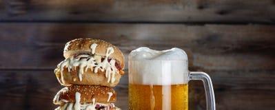 一个杯子低度黄啤酒和一个巨大的汉堡 免版税库存图片