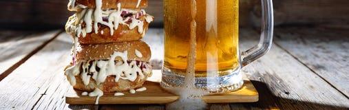 一个杯子低度黄啤酒和一个巨大的汉堡 库存照片