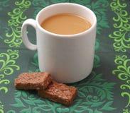 一个杯子加奶咖啡和黑色结块 免版税库存照片