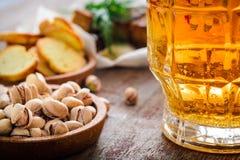 一个杯子啤酒和盐味的开心果在一张木桌上 免版税库存图片