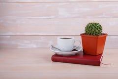 一个杯子在一个红色笔记本的无奶咖啡 库存照片