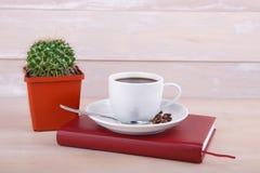 一个杯子在一个红色笔记本的无奶咖啡 免版税图库摄影
