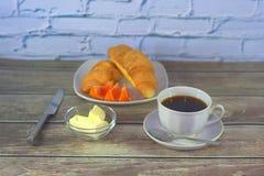 一个杯子在一个茶碟的无奶咖啡有一把匙子、一块板材用新月形面包和柠檬切片的与黄油立场在一张木桌上 免版税库存照片