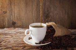 一个杯子在一张木桌上的热的咖啡用烤咖啡豆 免版税库存照片