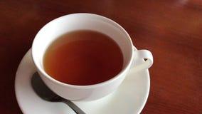 一个杯子在一张棕色桌上的红茶立场 股票视频