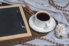 一个杯子在圣诞节装饰的无奶咖啡和与自由空间的板岩文本的 免版税库存照片
