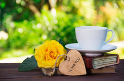 一个杯子在堆的夏天茶书和一朵芬芳黄色玫瑰 浪漫概念 复制空间 库存照片