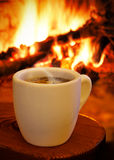 一个杯子在壁炉前面的热咖啡 图库摄影