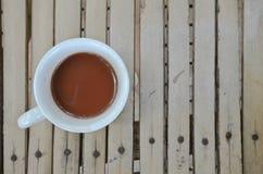 一个杯子在木地板上的热巧克力 库存照片