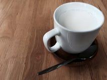 一个杯子在木桌上的牛奶 库存照片