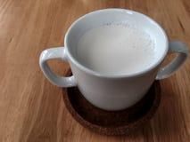 一个杯子在木桌上的牛奶 免版税图库摄影