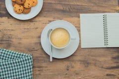 一个杯子在木桌和笔记本上的热奶咖啡 免版税图库摄影