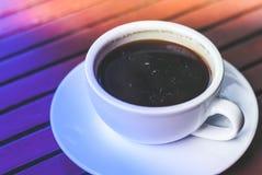 一个杯子在板材的热的浓咖啡咖啡在早晨仓促时间的木桌上与五颜六色的照明设备 库存照片