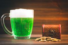 一个杯子在桌上的绿色啤酒 三叶草叶子 金子,硬币堆的胸口 StPatrick 's天 免版税库存照片