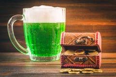 一个杯子在桌上的绿色啤酒 三叶草叶子 金子,硬币堆的胸口 StPatrick 's天 免版税图库摄影