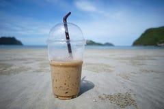 一个杯子在沙子的被冰的咖啡与迷离在Prachuapkhirikhan泰国的海和海岛backgroud 免版税图库摄影