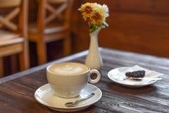 一个杯子在葡萄酒咖啡馆的一张黑暗的木桌上的cappucino 库存照片