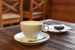 一个杯子在葡萄酒咖啡馆的一张黑暗的木桌上的cappucino 免版税库存照片