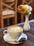 一个杯子在葡萄酒咖啡馆的一张黑暗的木桌上的cappucino 免版税图库摄影