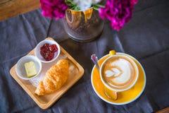 一个杯子拿铁艺术用在咖啡馆的一个新月形面包 免版税图库摄影