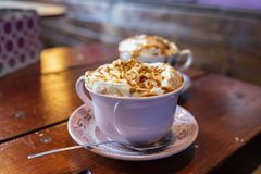 一个杯子新鲜的巧克力热饮冠上与打好的奶油和盐味的焦糖 免版税库存图片