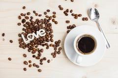 一个杯子无奶咖啡用桂香和咖啡豆在一张木桌上 免版税库存照片