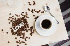 一个杯子无奶咖啡用桂香和咖啡豆在一张木桌上 免版税库存图片