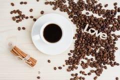 一个杯子无奶咖啡用桂香和咖啡豆在一张木桌上 库存图片