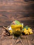 一个杯子柠檬茶用在木被弄脏的背景的薄菏 与阳桃和肉桂条的热的茶 复制空间 免版税库存照片