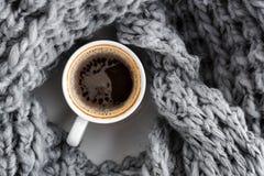 一个杯子浓咖啡,包裹在一条羊毛温暖的灰色围巾 顶视图 库存照片