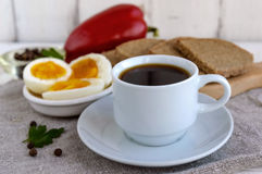 一个杯子浓咖啡& x28; espresso& x29; 特写镜头和容易的饮食用早餐-煮沸的鸡蛋和黑麦面包 免版税库存图片