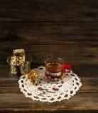 一个杯子清凉茶和在背景o的糖煮的烤坚果 免版税库存照片