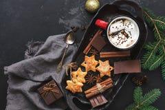 一个杯子热巧克力用蛋白软糖,星曲奇饼,香料,巧克力切片,冷杉在黑具体背景分支 Chr 免版税图库摄影