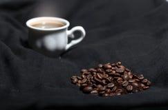 一个杯子热气腾腾的咖啡和咖啡豆 库存图片